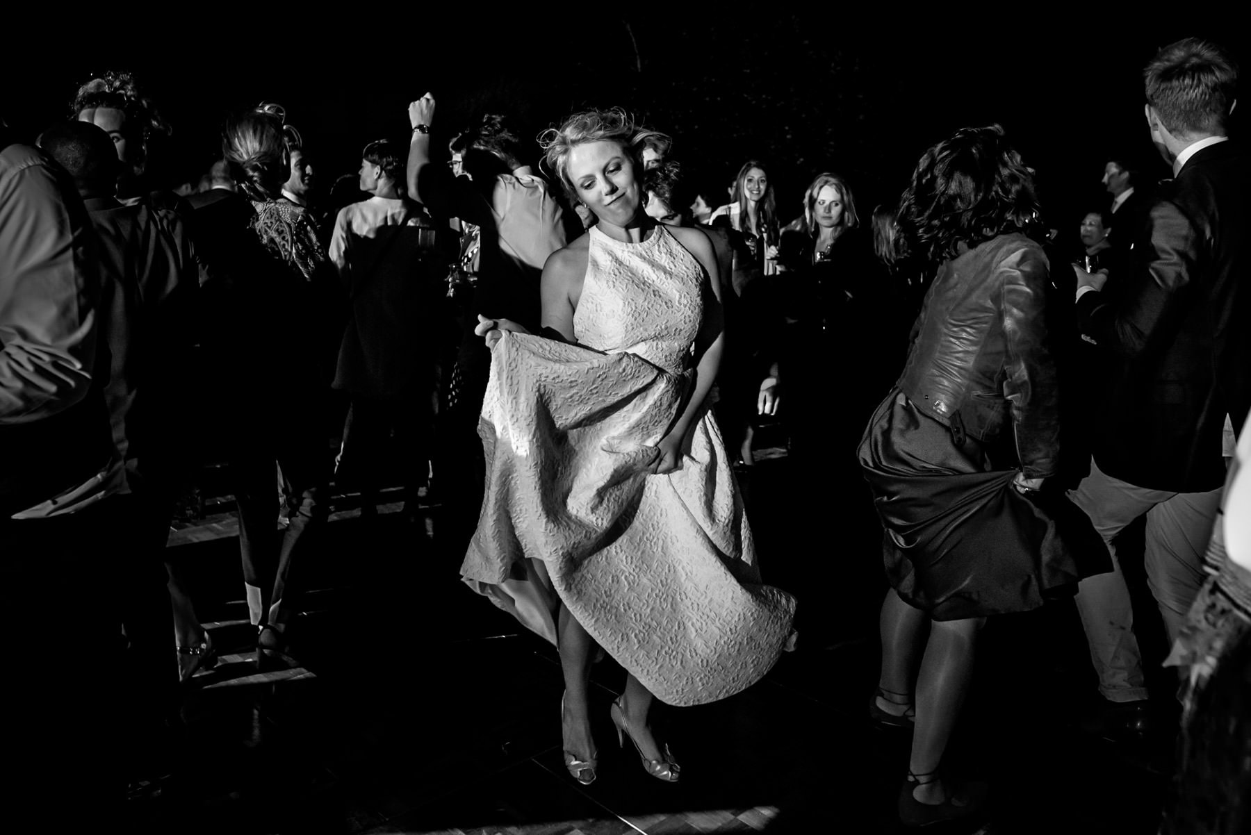 black and white photo of bride dancing on her own at her garden wedding