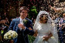 bride and groom being hit with alternative wedding confetti in the sun