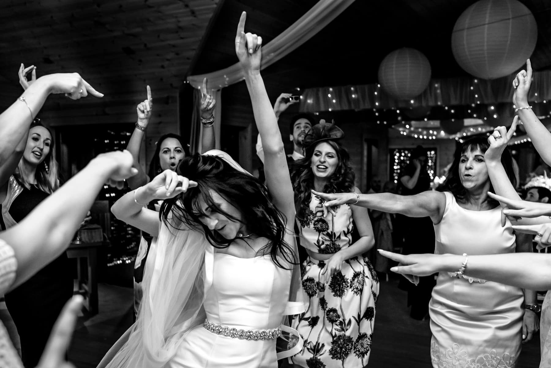 A black and white photo of a bride dancing surrounded by all her friends with their arms in the air