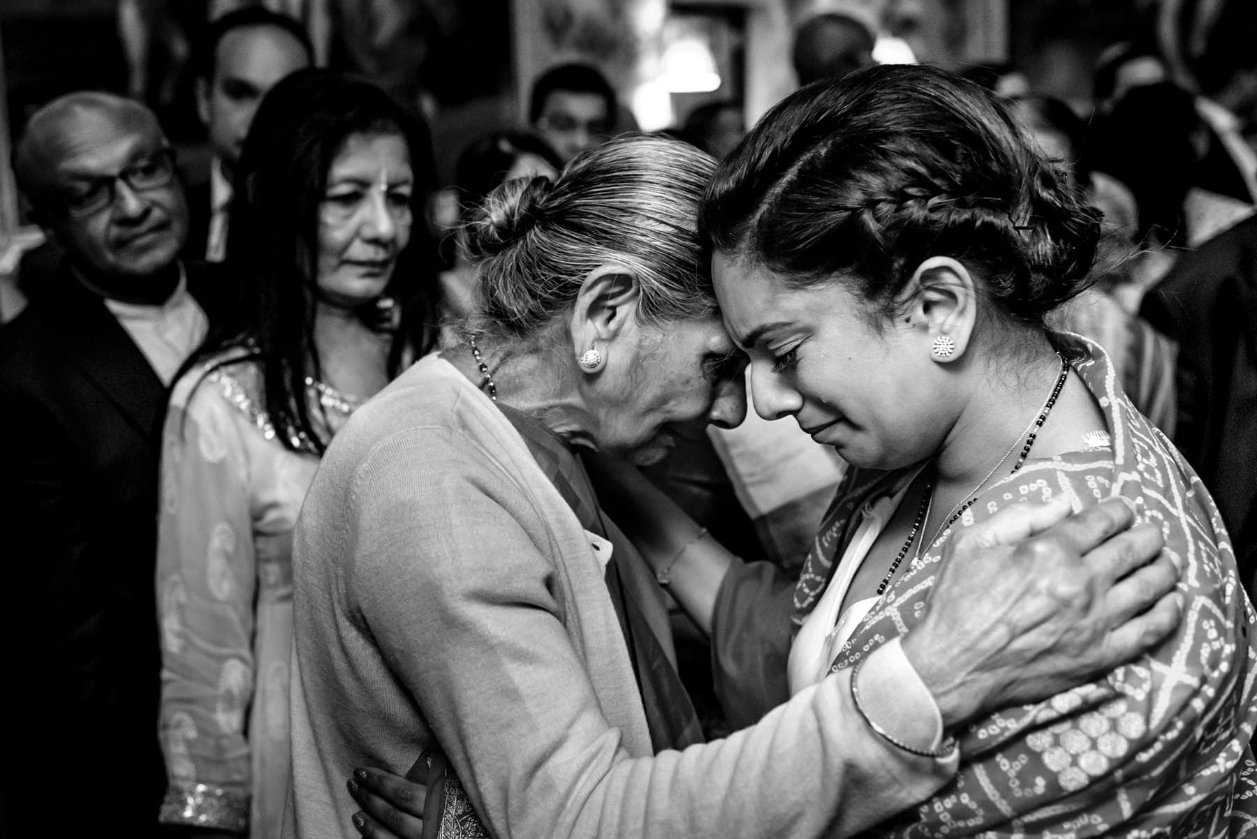 Bride crying as she says goodbye to her grandmother at the end of her wedding