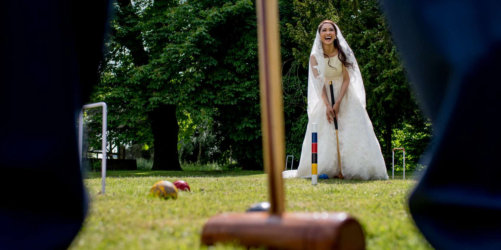 a bride in her wedding dress playing croquet in the sun and laughing taken by London wedding photographer Matt Badenoch