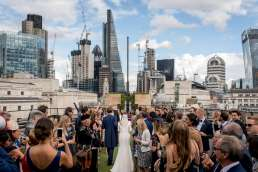 bride and groom walking between guests with backdrop of the city of London featured for a wedding blog