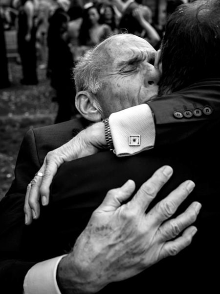 Photo of groom's father hugging the groom at his wedding