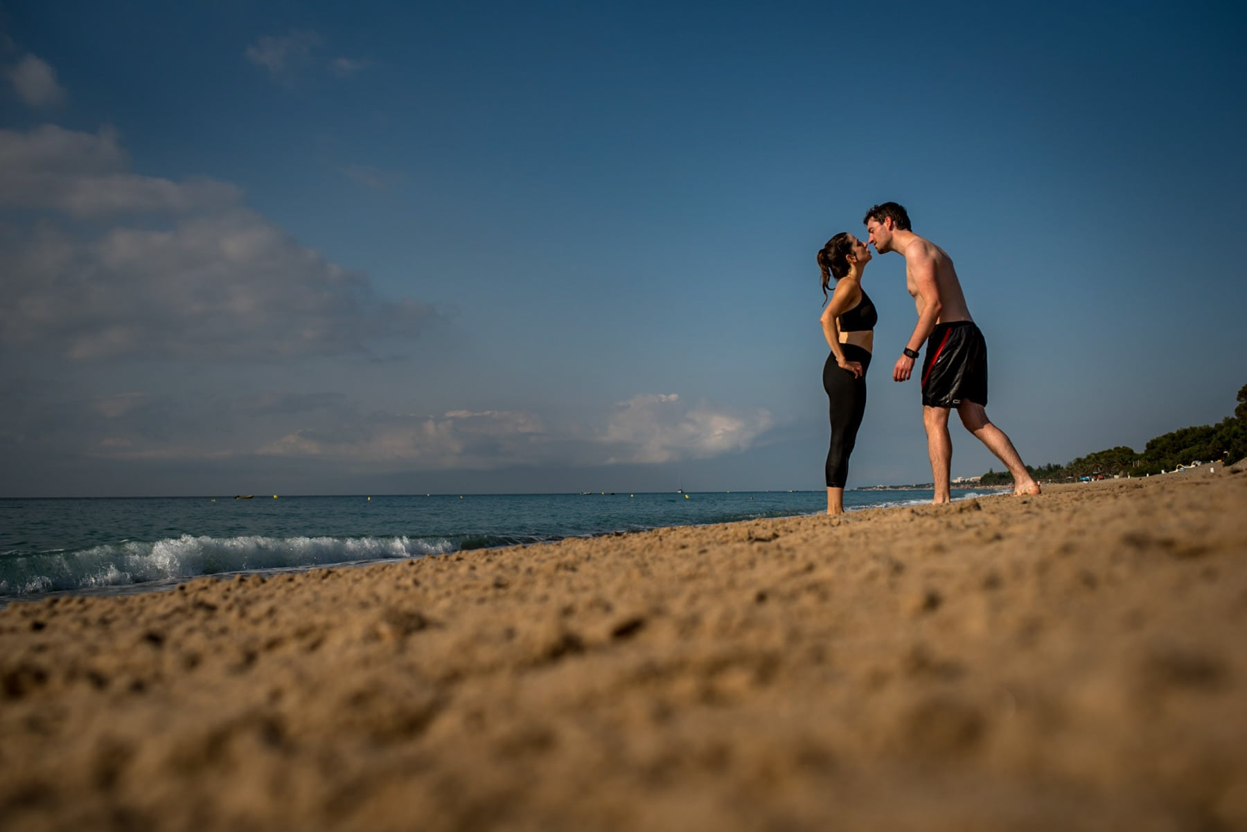 couple kissing on a beach in Barcelona, Spain