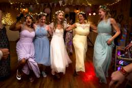 bride dancing with her bridesmaids in colourful dresses at her wedding