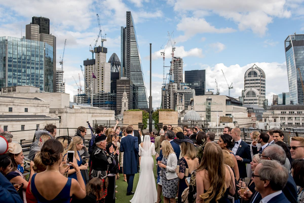 bride and groom walking in wedding reception with London city as a backdrop