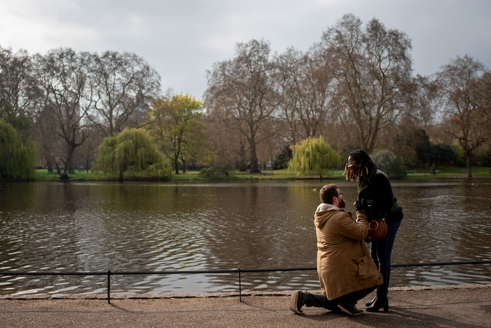 Photo of a man kneeling and proposing to his girlfriend by the lake in St James Park in London