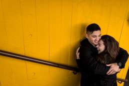 couple hugging against yellow wall, best london locations for a proposal
