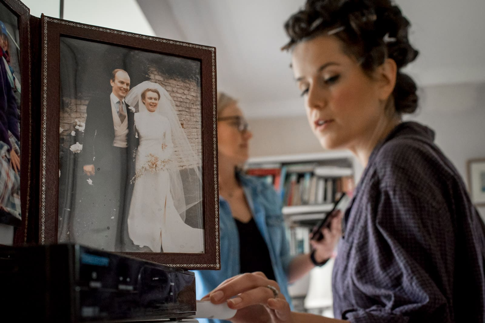 photo of bride's parents getting married next to her getting reading the morning of her wedding
