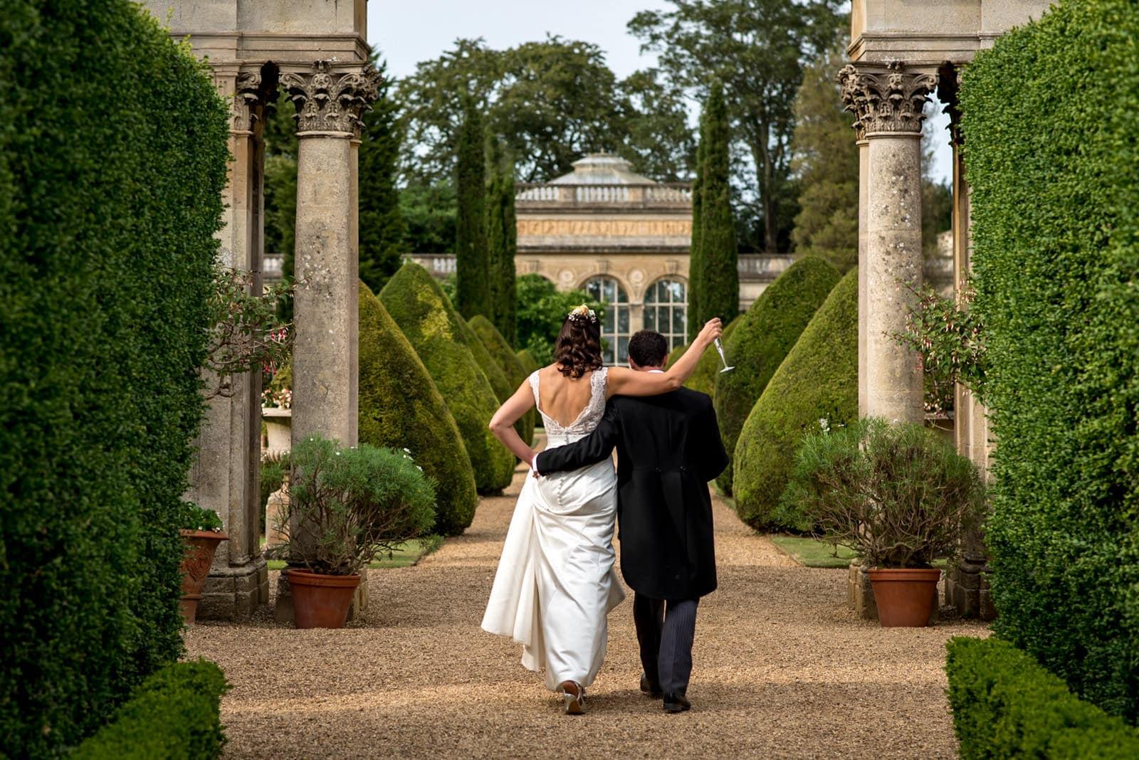 bride and groom walking together in the grounds of castle Ashby