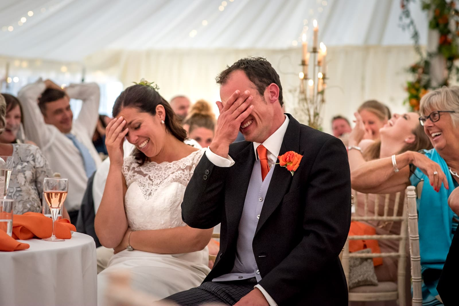 bride and groom laughing with embarrassment and covering their faces during the speeches