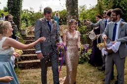 photo of wedding guests throwing petals as confetti at the bride and groom
