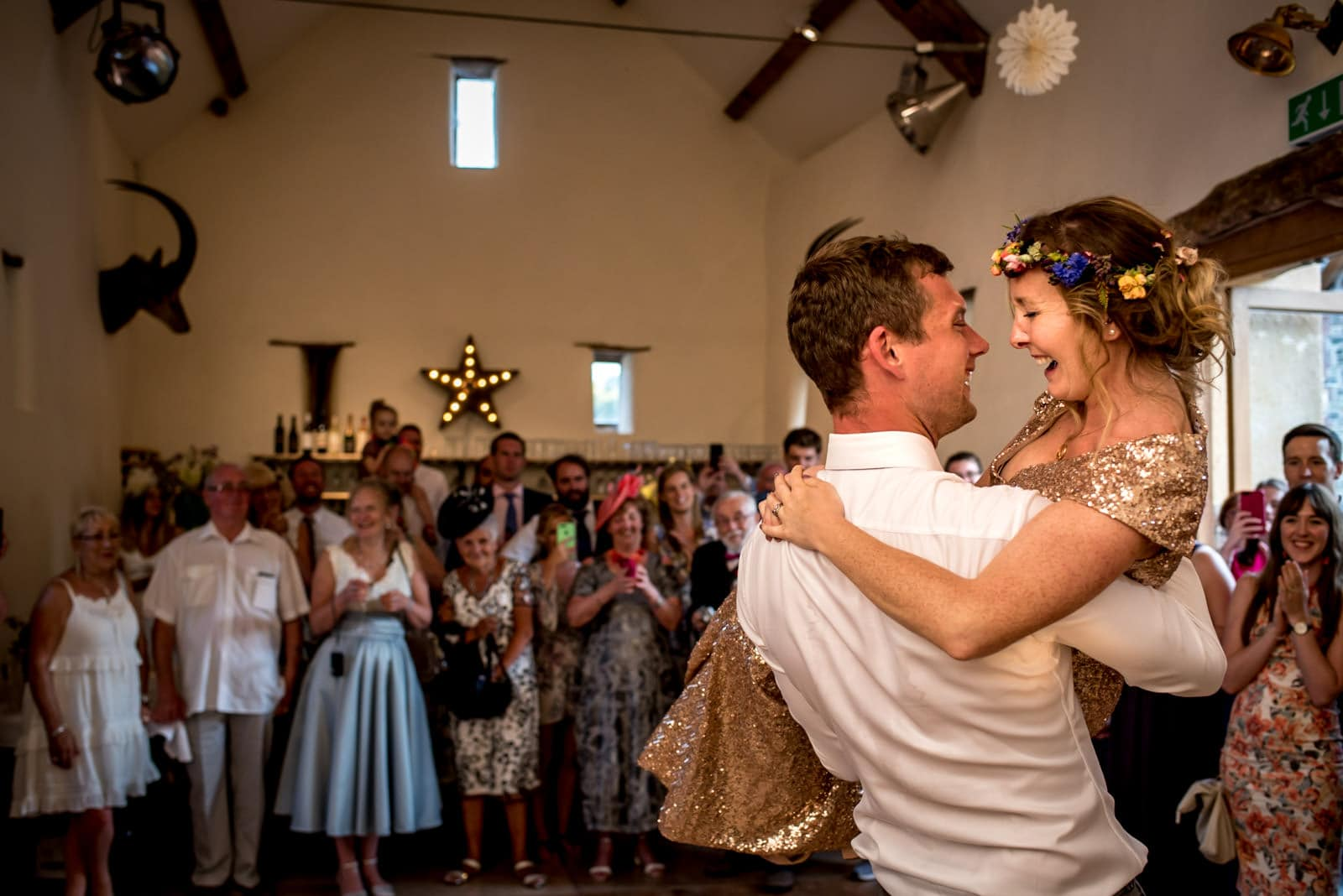 photo of the groom lifting up his bride during the first dance
