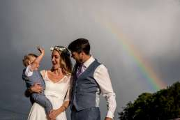 photo of bride and groom with their son in front of a rainbow on their wedding day
