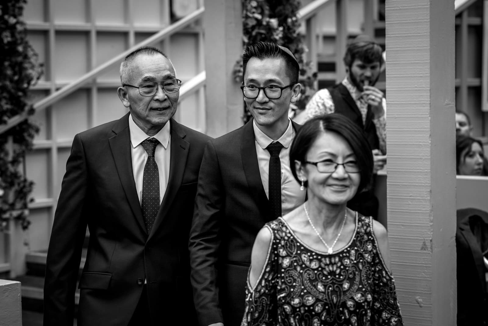 black and white photo of groom walking down aisle with his parents at his wedding