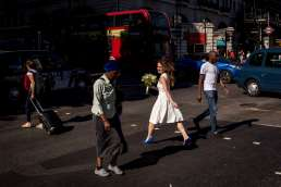 photo of bride in wedding dress walking across the street in London with a red bus in background.