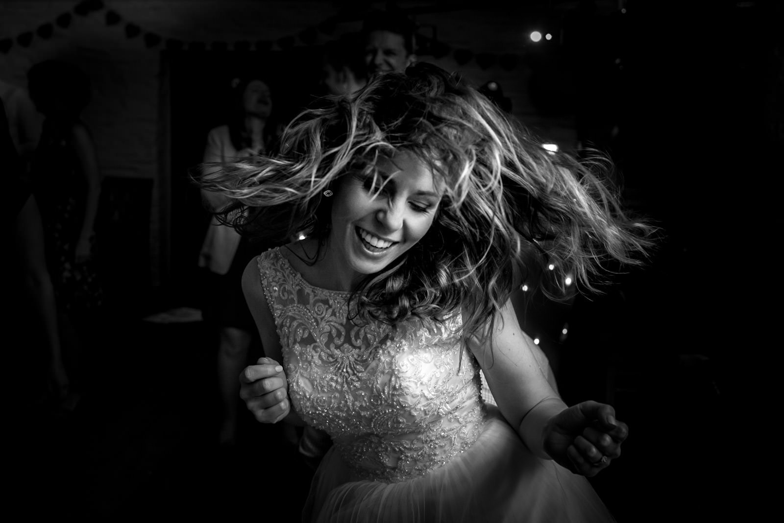 black and white photo of bride dancing on the dance floor with her flying everywhere at her wedding