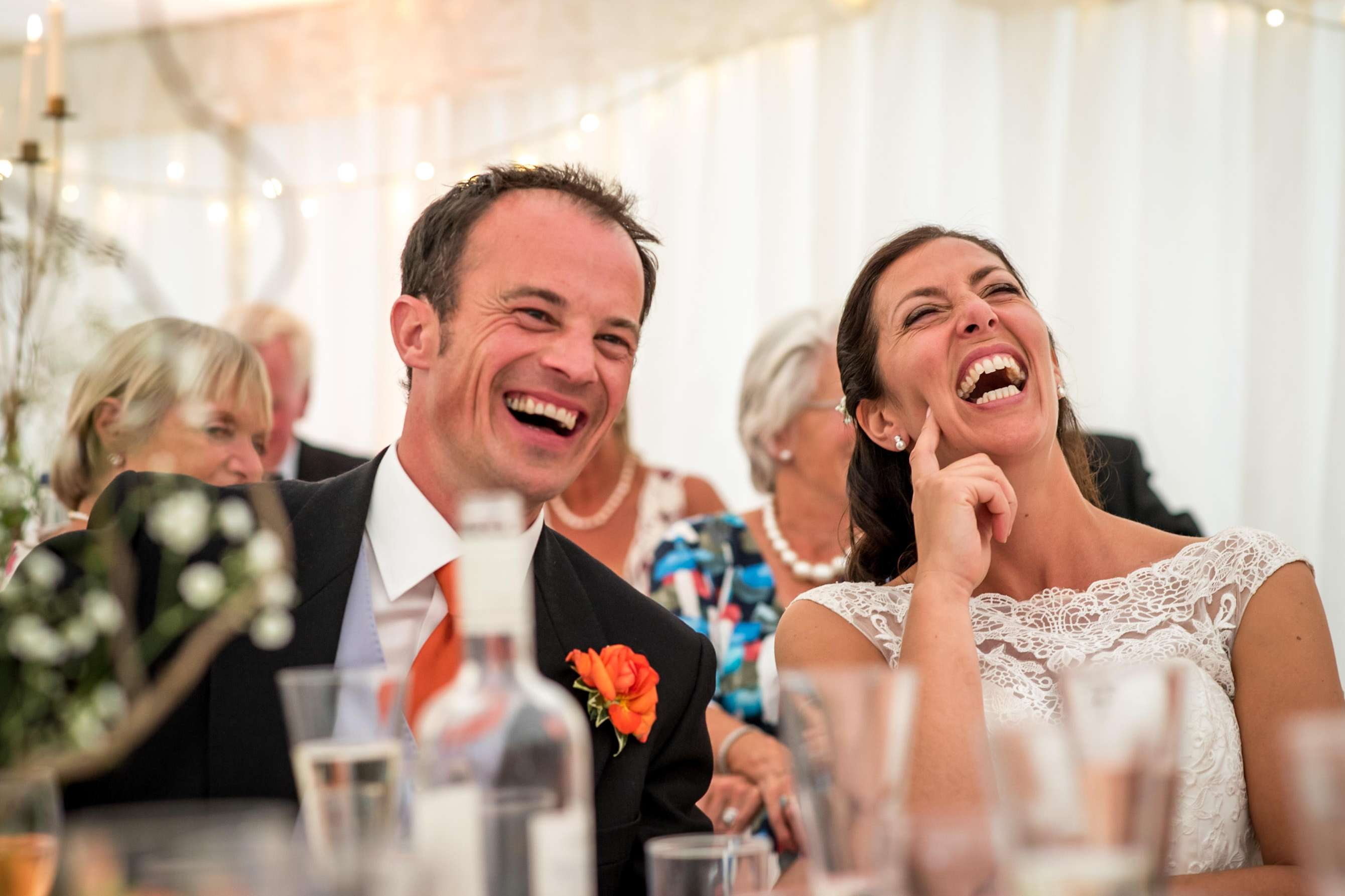A bride and groom's favourite wedding photo showing them laughing during the speeches
