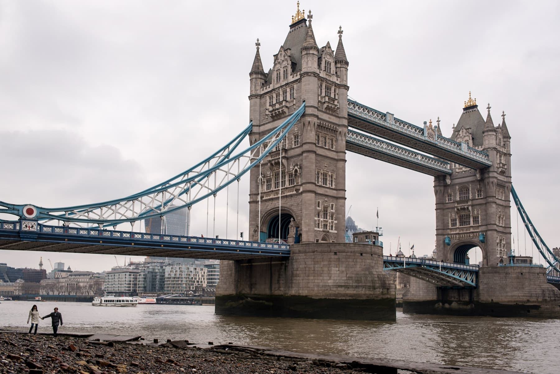 Couple walking on the Thames beach at low tide next to the Tower of London during their proposal shoot