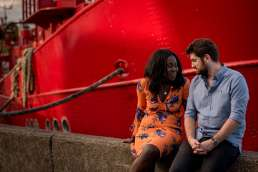 Photo of an engaged couple city next to a red boat at Trinity Buoy Wharf in London
