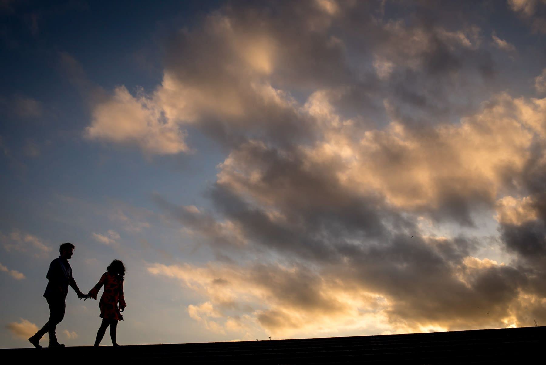 Photo of a couple's silhouette walking against a blue sky and clouds during their proposal shoot
