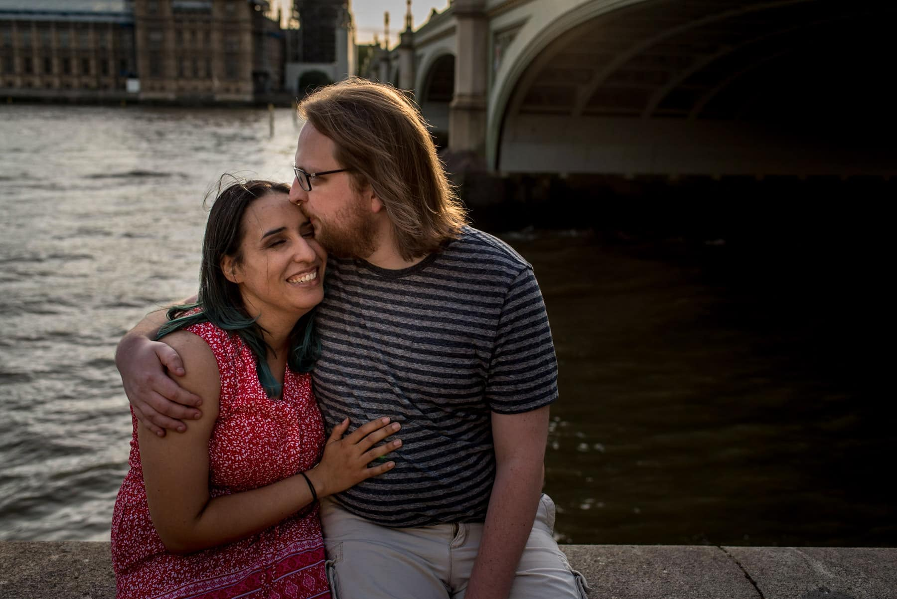 Photo of a couple hugging next to Westminster bridge in London during their photography session