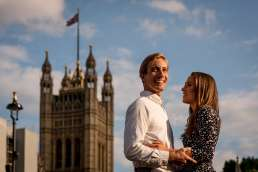 Photo of a couple smiling outside of Parliament during their London proposal shoot