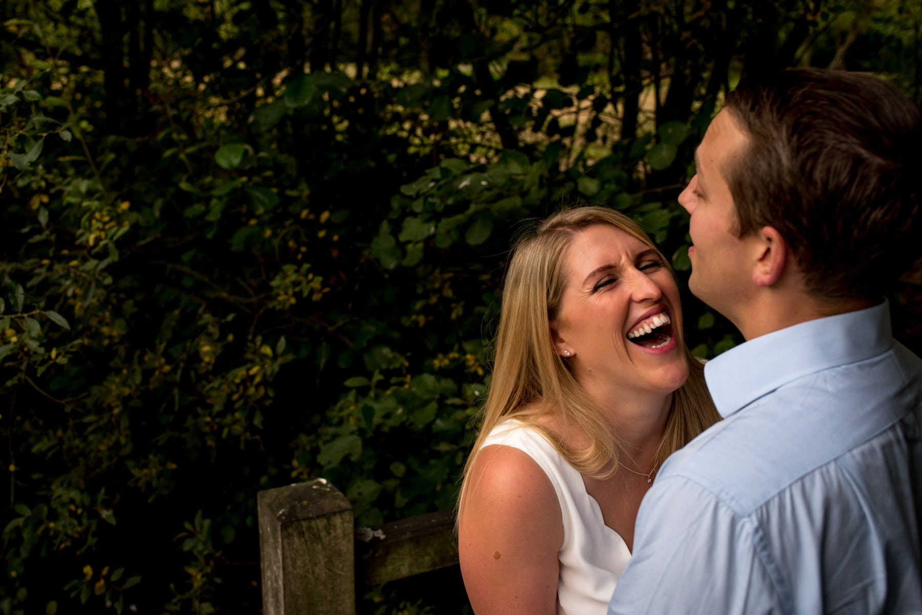 Photo of a women laughing really hard as her fiance hugs her in a park