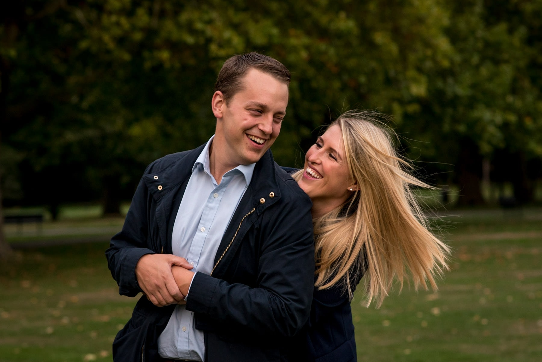 Photo of a women hugging her fiance and laughing in a London park