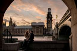 An engagement couple on their proposal shoot in front of Parliament and Big Ben in London at sunset