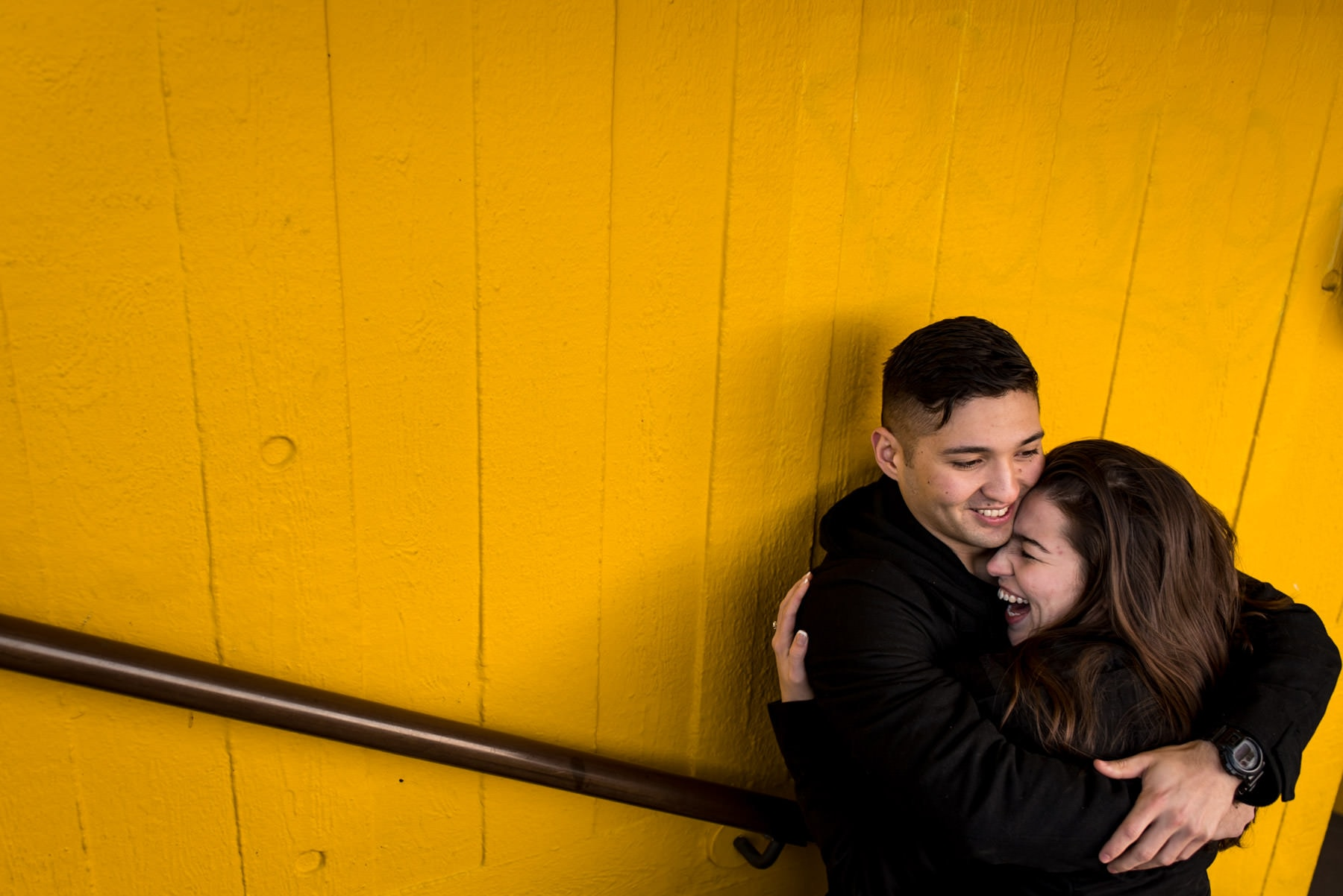 Photo of a couple hugging on their London proposal photography shoot with a yellow wall