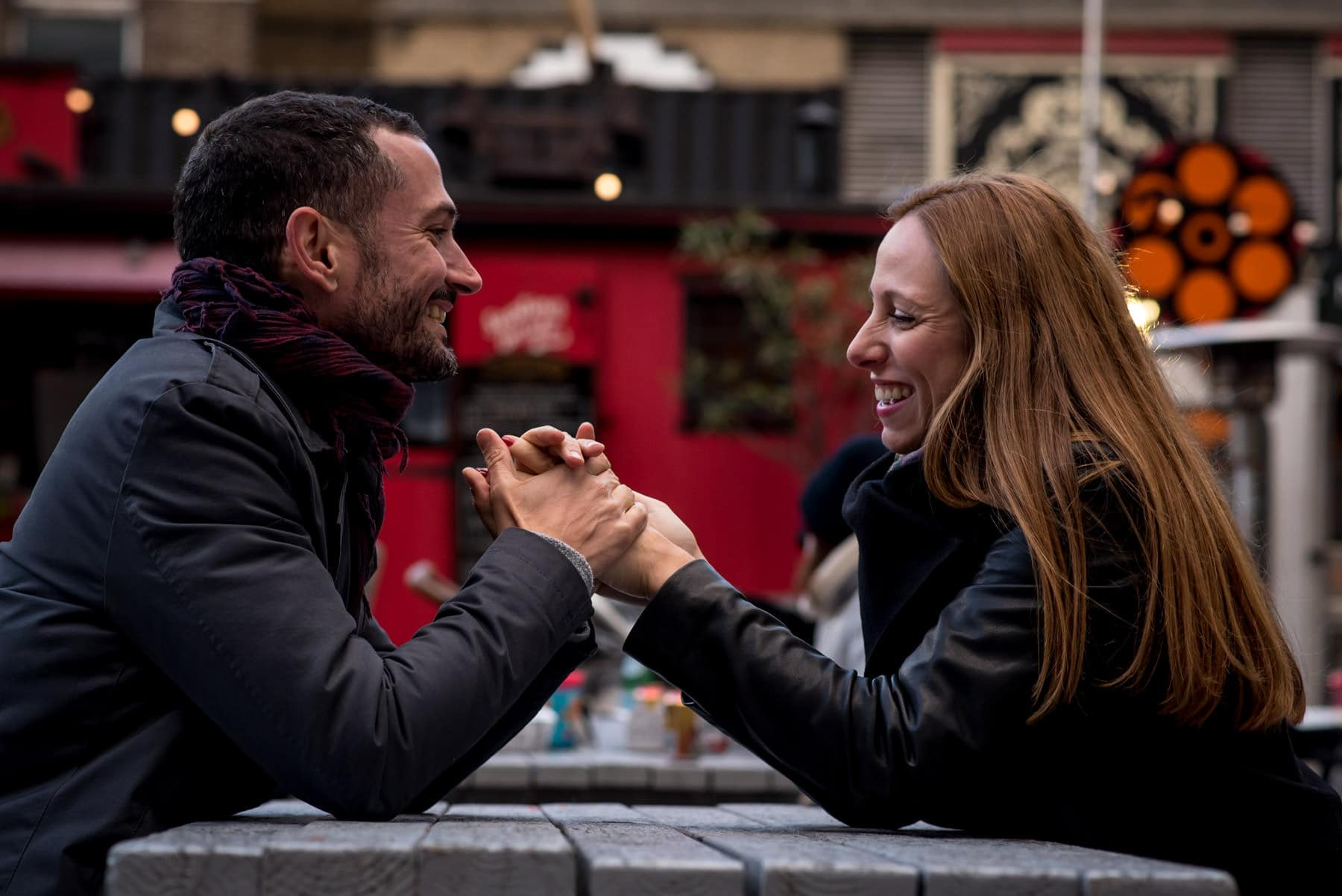 Photo of a couple holding their hands and laughing in Shoreditch, London