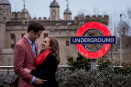 A couple laughing on their engagement shoot in from of the Tower of London and an Underground sign.