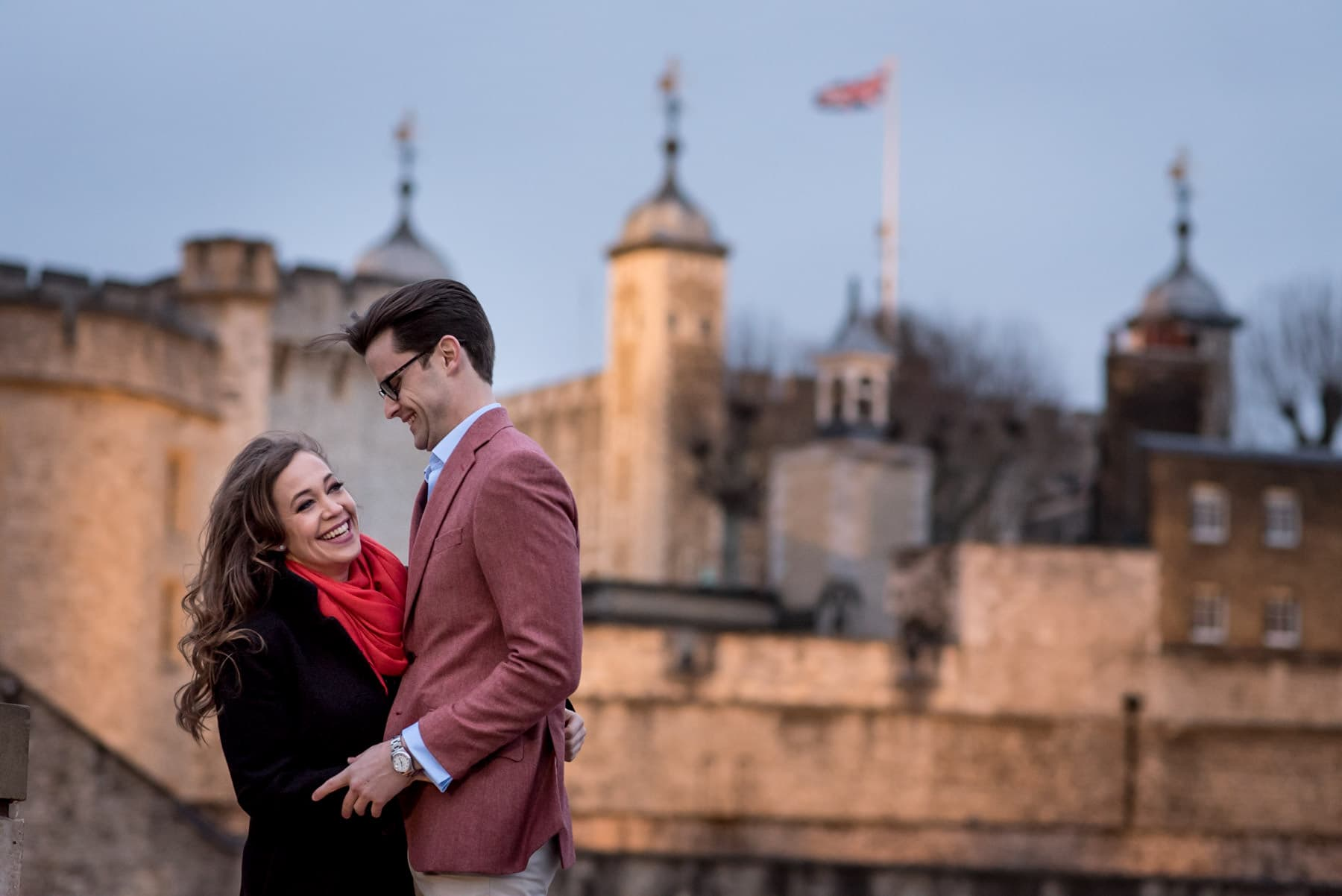 a couple laughing on their london proposal shoot in front of the Tower of London
