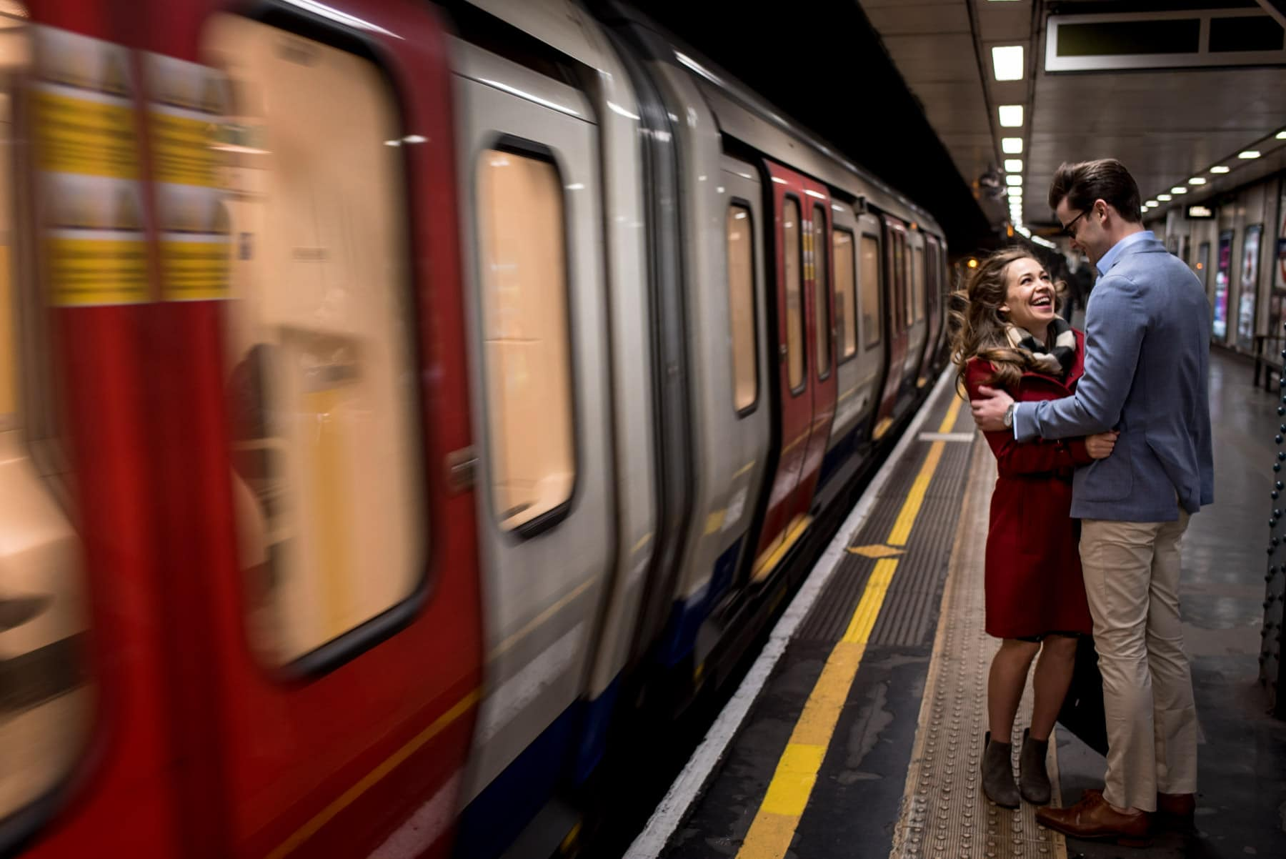 photo of a recently engaged couple laughing as a train goes past on the London Underground.