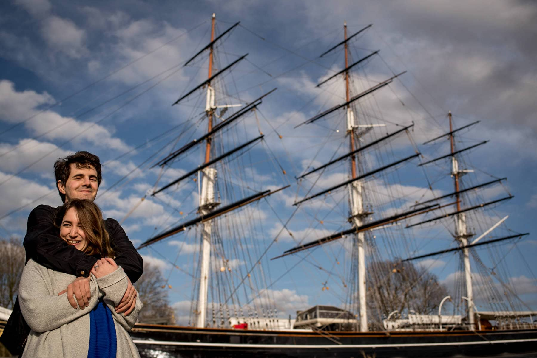 Photo of a couple hugging in front of the Cutty Sark in Greenwich, London during their proposal photography shoot