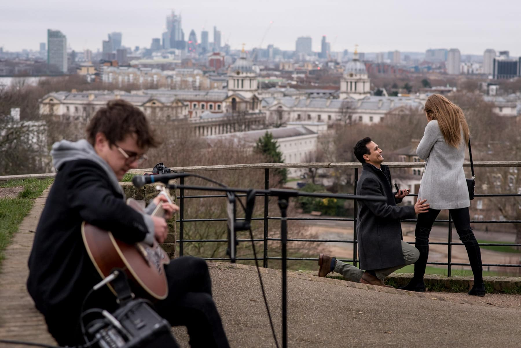 A man on his knees proposing to his girlfriend with views over London and a guitar player. Photo taken in Greenwich park.