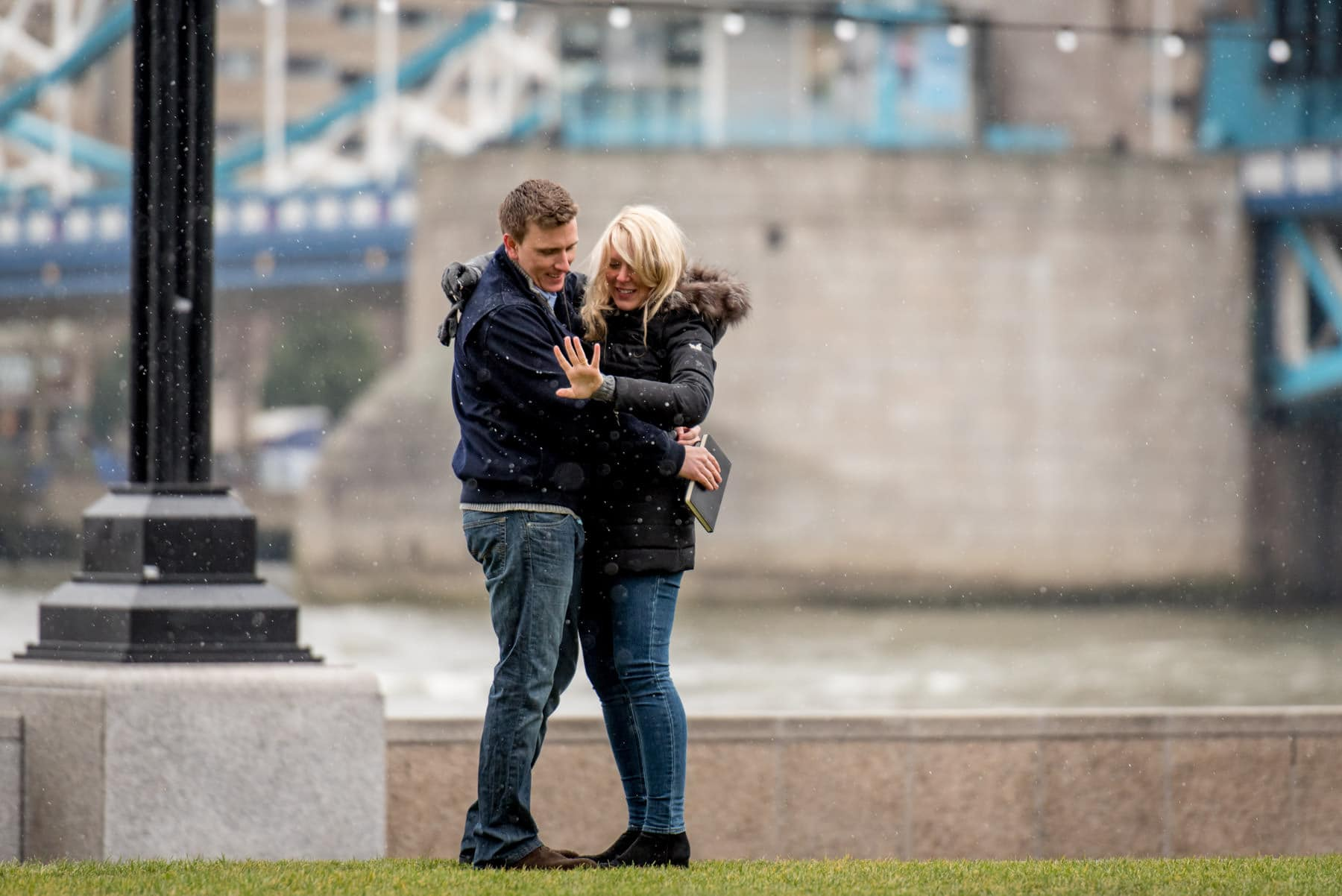 A American tourist who just proposed to his girlfriend in front of Tower Bridge in London in the rain