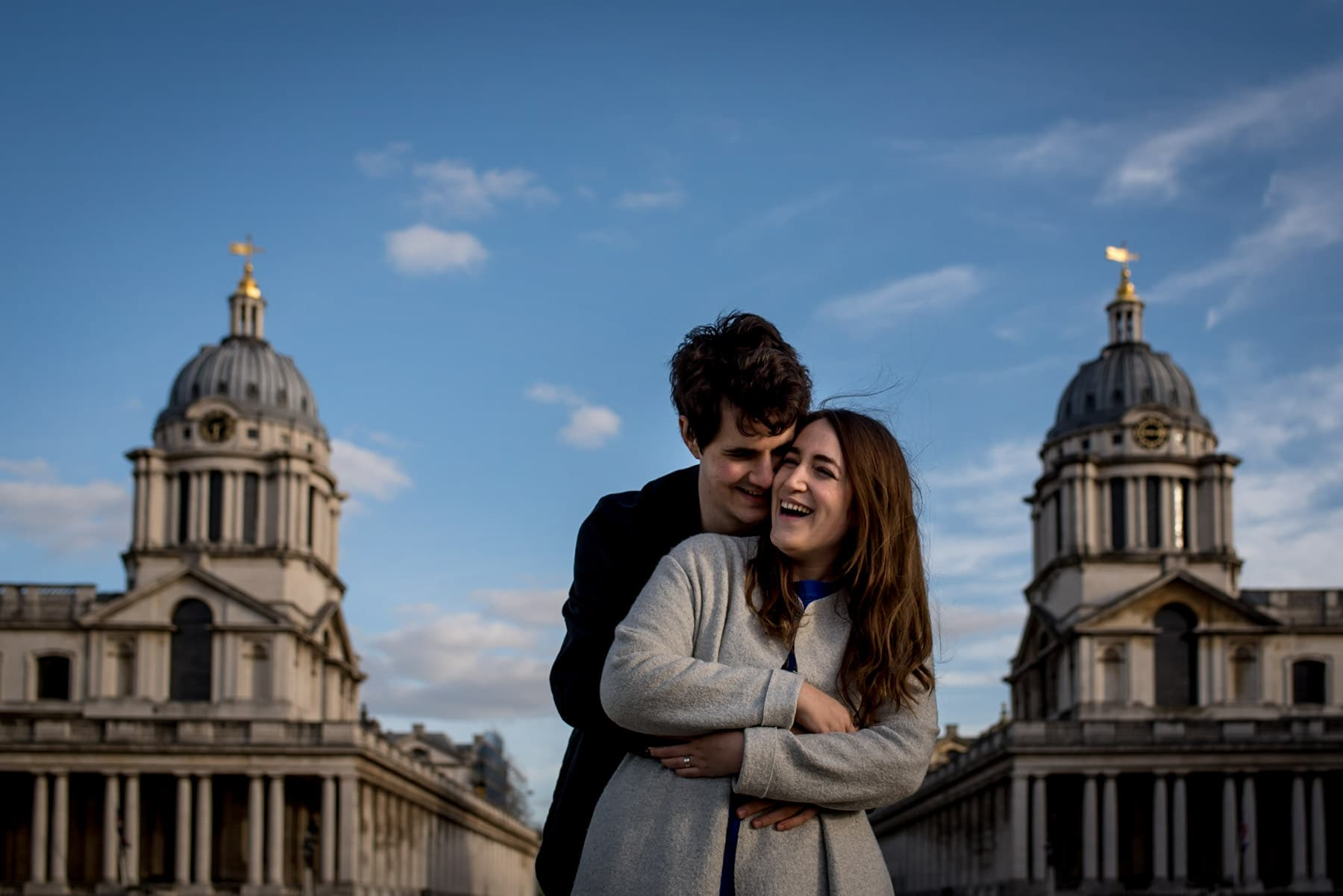 Photo of a an engaged couple laughing at the Old Royal Naval College in Greenwich during their proposal shoot