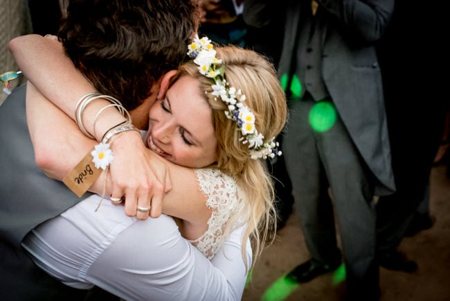 Photo of bride hugging groom at festival wedding