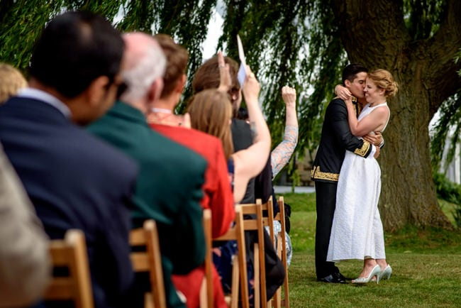 Bride and groom kissing during their back garden wedding