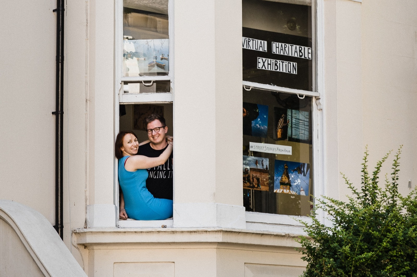 photo of Matt and Corina with photos from their exhibition street stories from afar