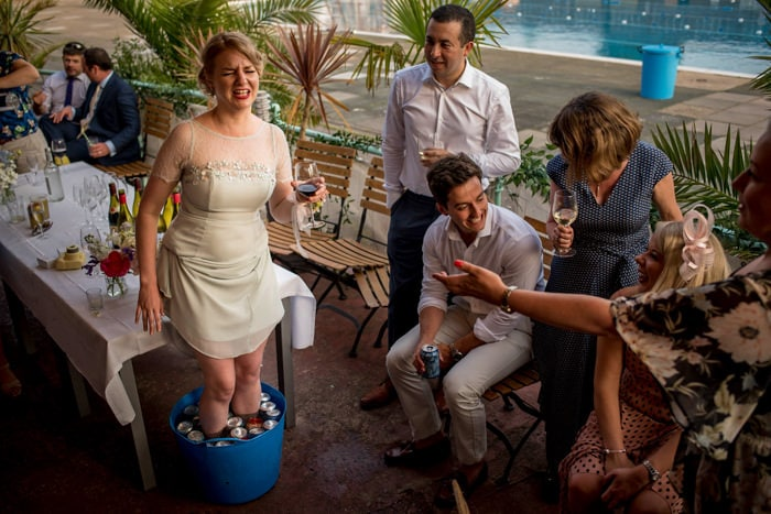 bridesmaid dunking her feet in ice water to cool them down at a wedding