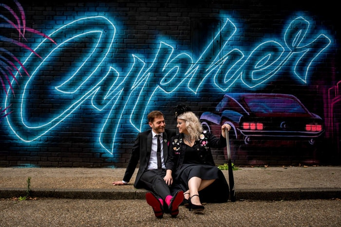Rock n roll bride and groom portraits in front of graffiti in london