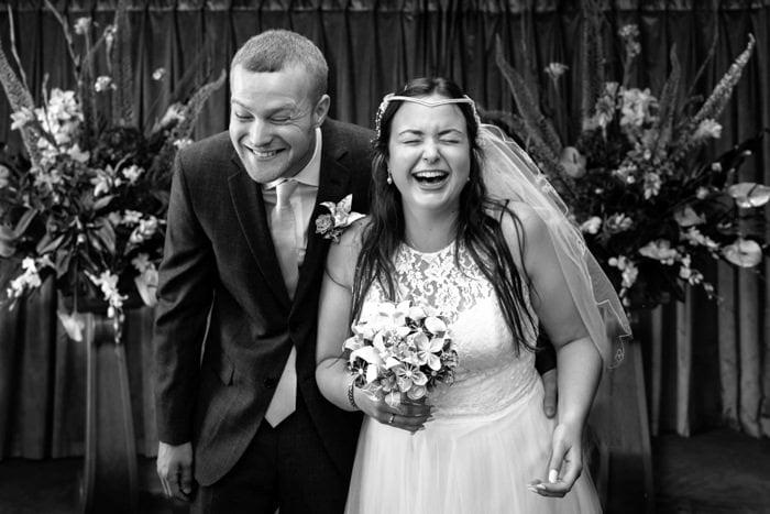 Black and white photo by london wedding photographer of couple laughing
