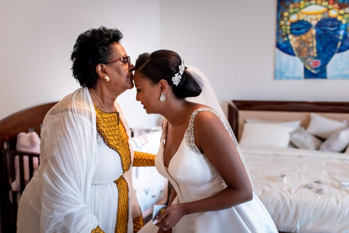 Ethiopian bride being kissed by her mum during bridal prep