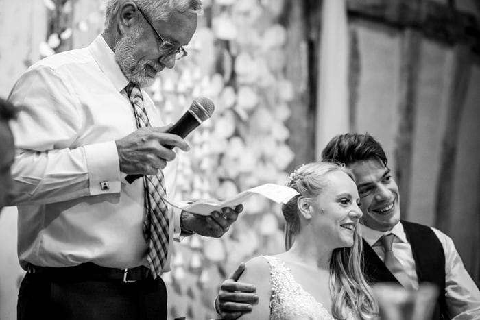 bride and groom smiling during their dad's speeches at their london wedding