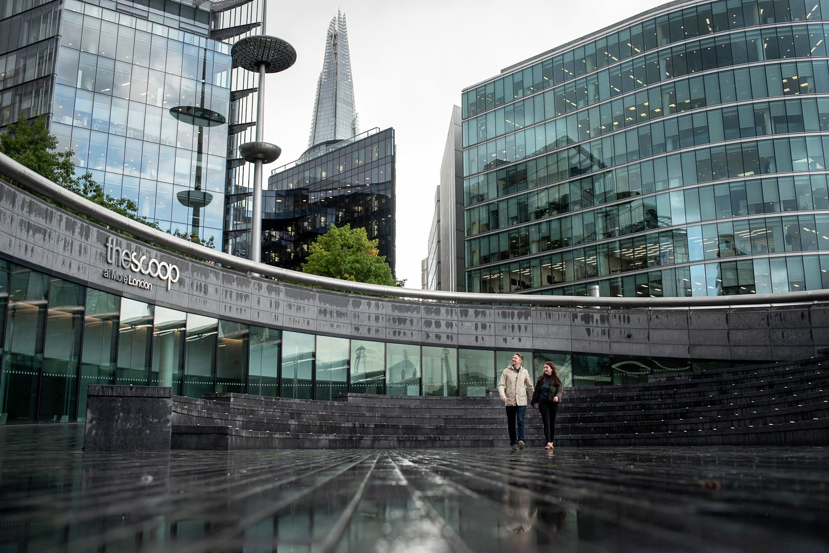 Couple walking on a rainy London day outside the Scoop and the Shard