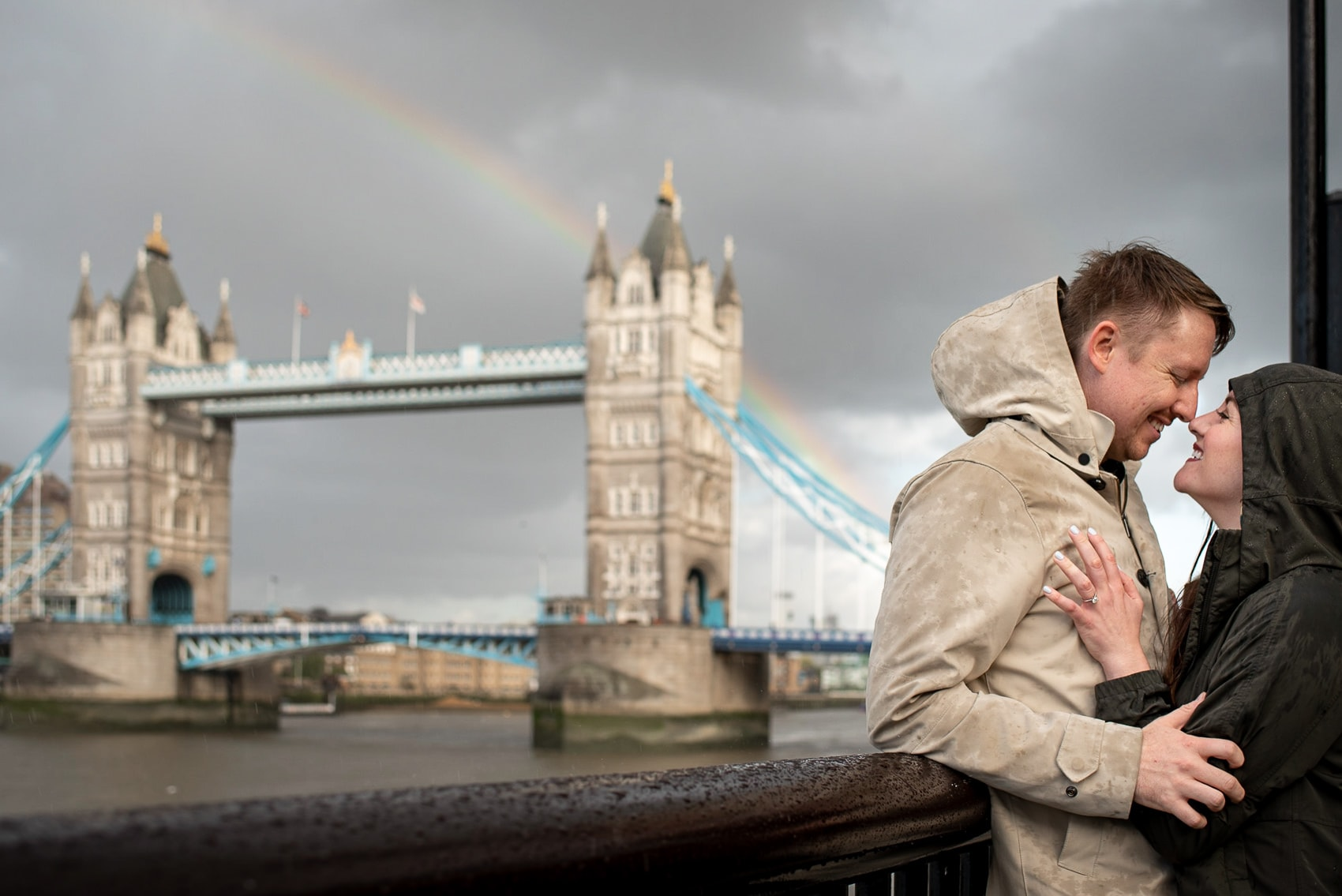 Photo of engaged couple laughing with Tower Bridge and a Rainbow in the background