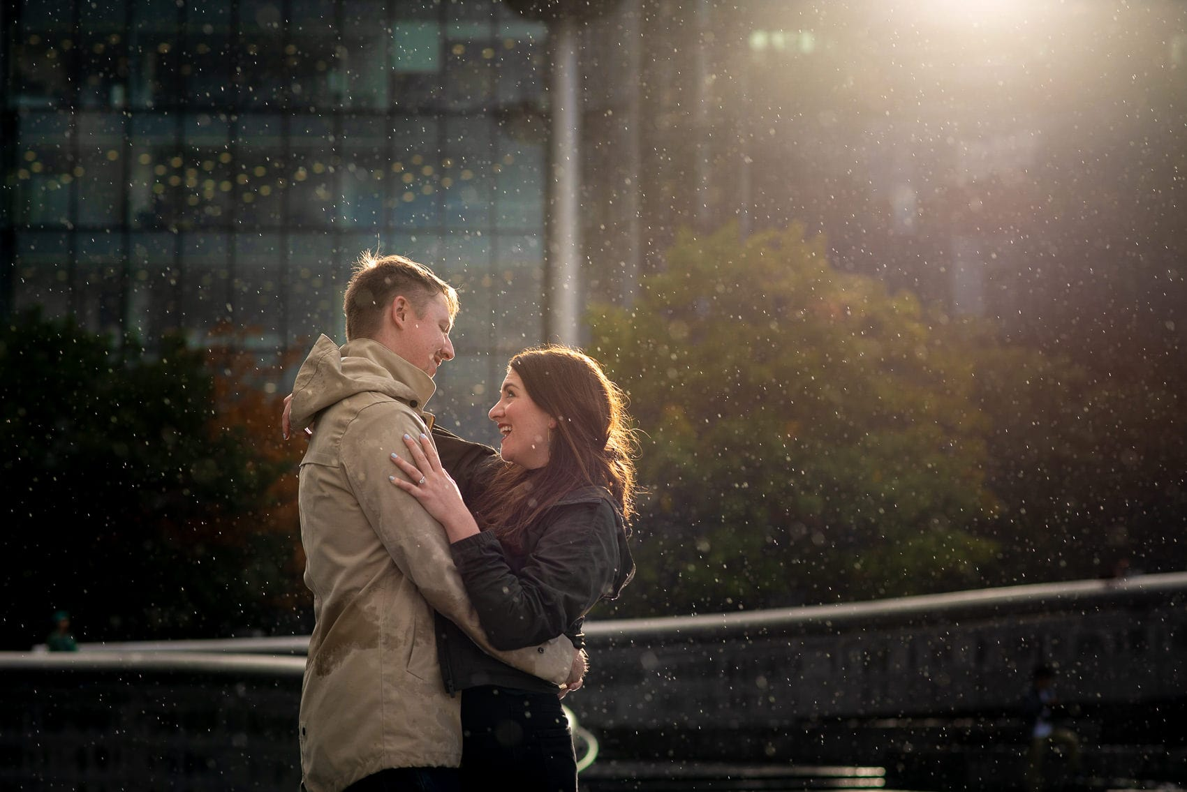 Couple laughing in the rain and sun on their south bank engagement shoot